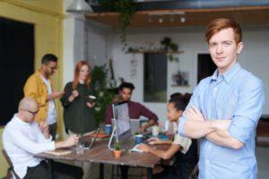 Mitarbeiter im Büro mit Team im Hintergrund